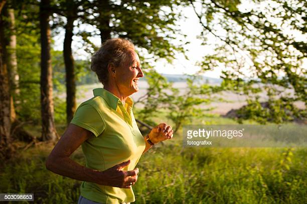 senior woman jogging through the forest