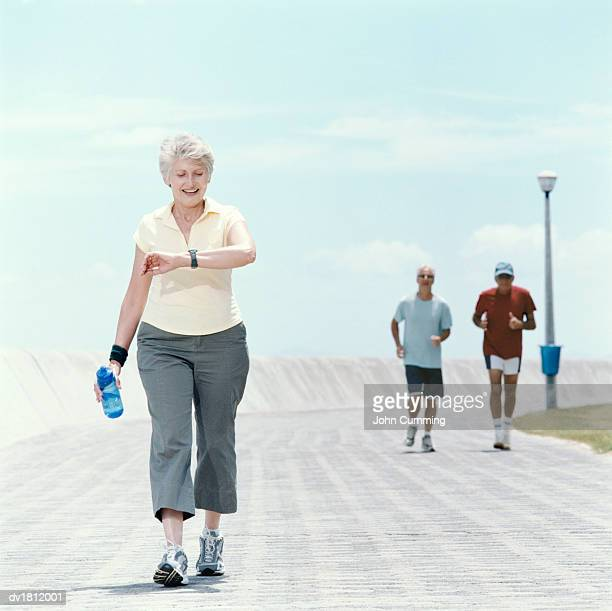 Senior Woman Jogs on a Path, Checking Her Time on a Watch