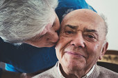 Senior woman kissing her husband