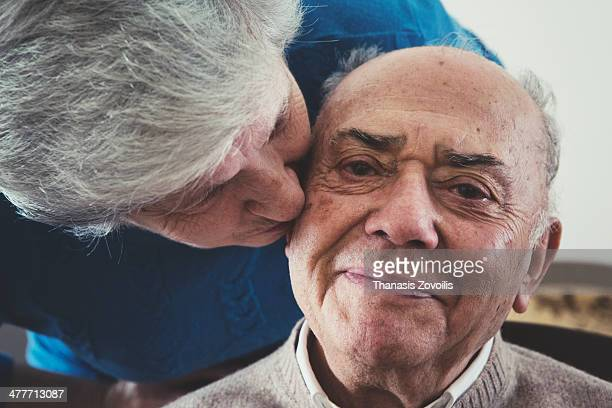 Senior woman kissing her husband