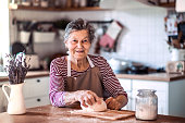 A portrait of a happy senior woman kneading dough in the kitchen at home.