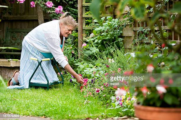 Senior woman kneeling on a kneeler in her garden outdoors.