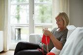 Senior woman knitting on sofa
