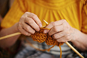 Close-up with selective focus of senior wrinkled female hands knitting with mustard colored yarn