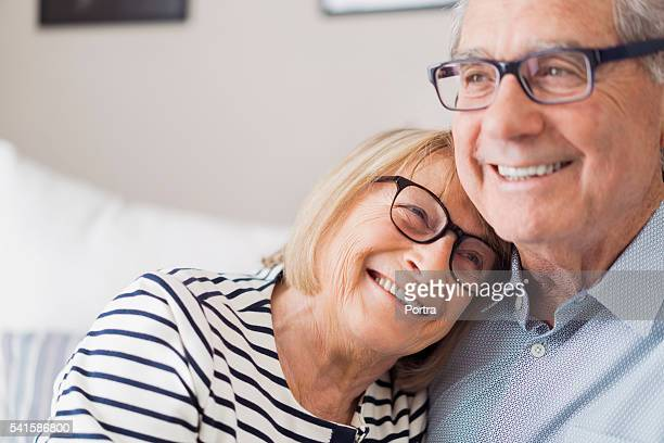 Senior woman leaning head on senior man's shoulder