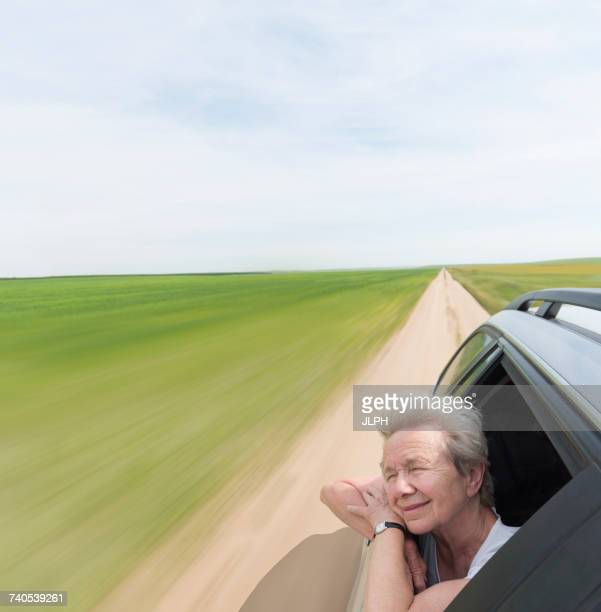 Senior woman leaning on car window enjoying wind in face