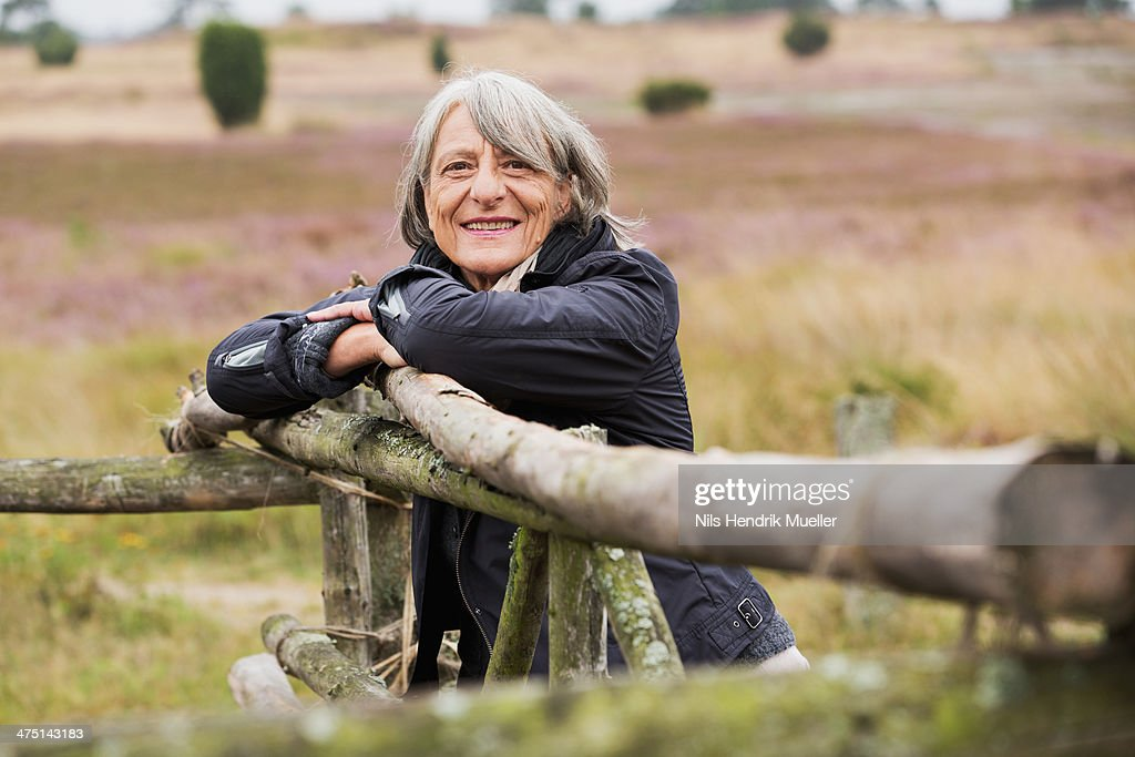 Senior woman leaning on wooden fence smiling towards camera