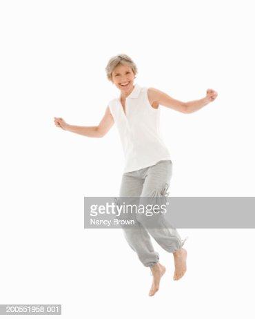 Senior woman leaping against white background, smiling, portrait : Stock Photo