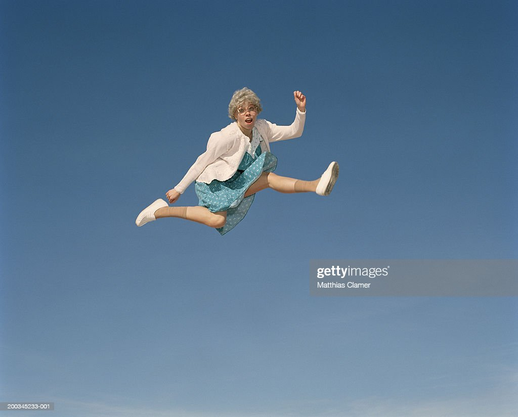Senior woman leaping in mid air, portrait : Stock Photo
