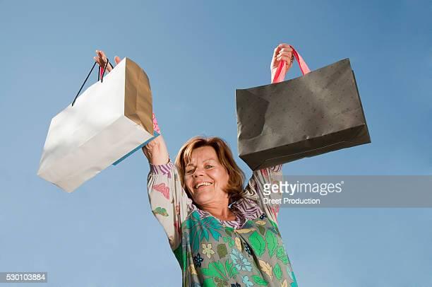 Senior woman lifting shopping bag, smiling, portrait