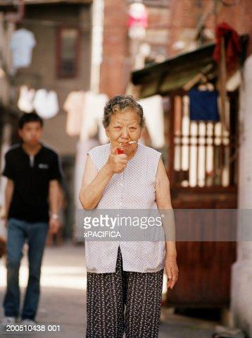 Senior woman lighting cigarette : Stock-Foto