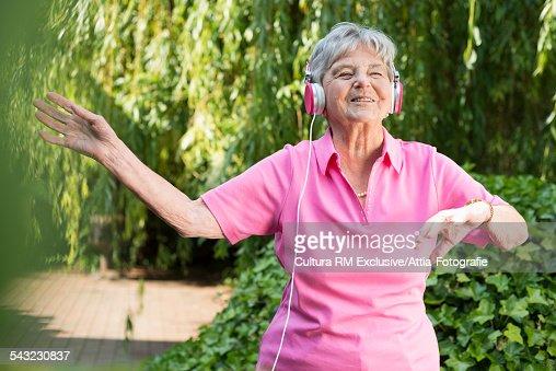 Senior woman listening to music on headphones in garden
