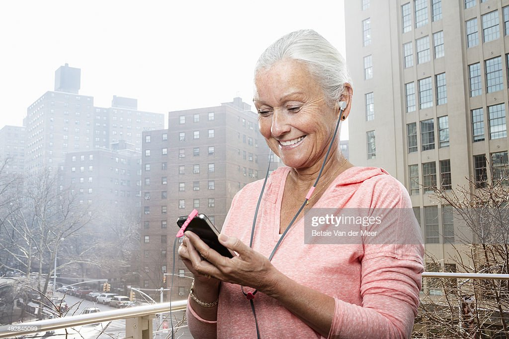 senior woman listening to phone city in background : Stock Photo