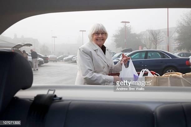 senior woman loading shopping into a car