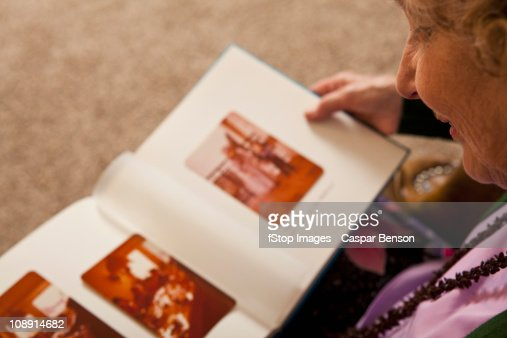 A senior woman looking at a photo album