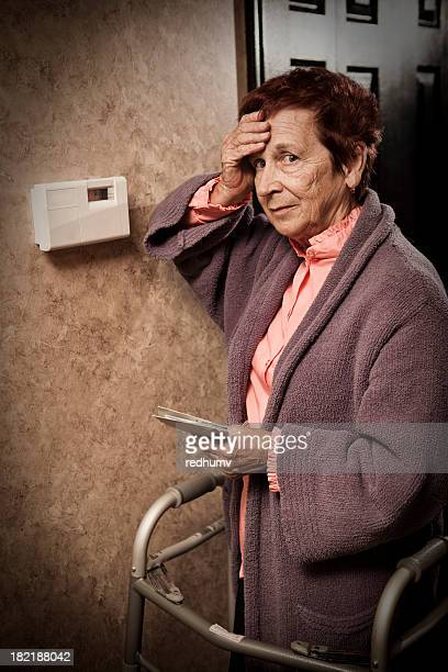 Senior Woman Looking at Bills and Thermostat