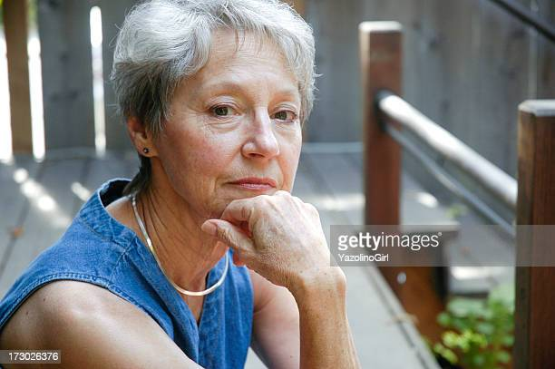 Senior woman looking at camera in a wooden porch