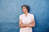 Portrait of mature senior standing with her arms crossed and looking away at copy space against blue background. Caucasian middle aged female looking at copy space on blue wall.