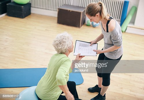 Senior woman looking at exercise plan with personal trainer : Stock Photo