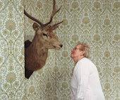 Senior woman looking at moose head on wall
