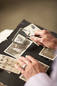 Senior woman looking at old photographs in album through magnifying glass, close-up of hands