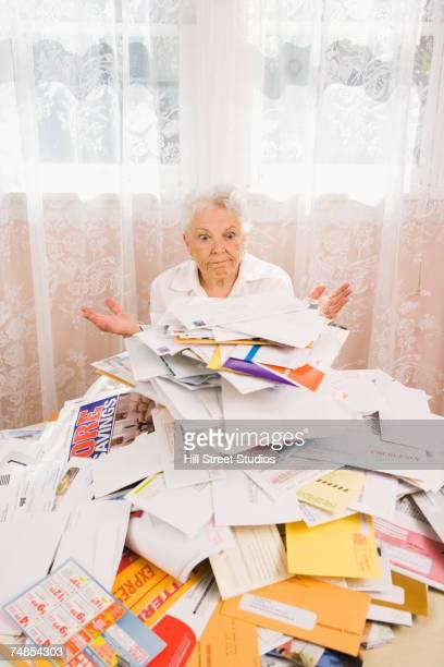 Senior woman looking at pile of bills