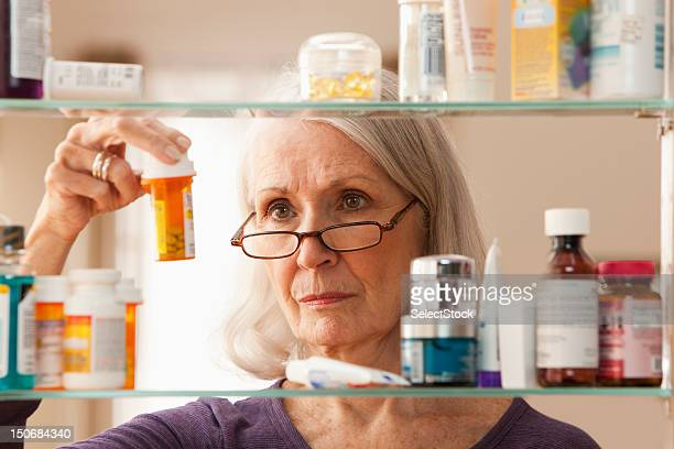 Senior woman looking at prescription bottles