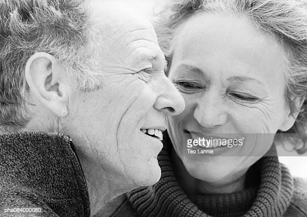 Senior woman looking at senior man smiling, portrait, B&W.