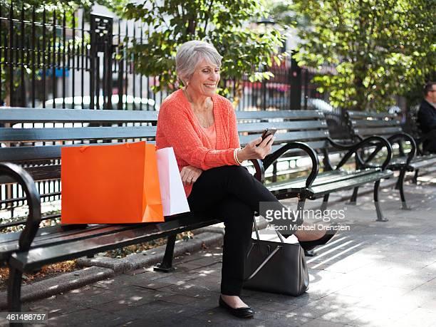 senior woman looking at smartphone on park bench