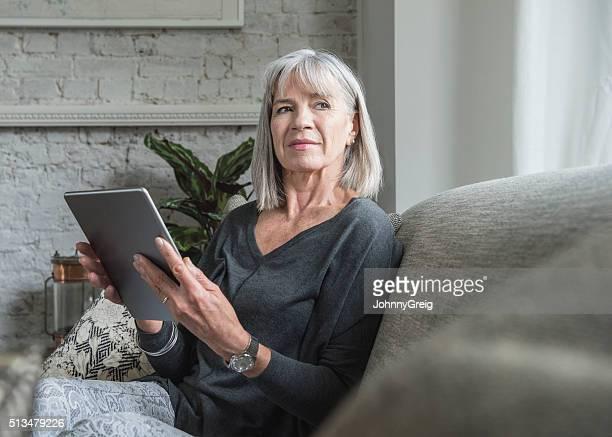 Senior woman looking away, holding digital tablet