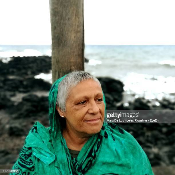 Senior Woman Looking Away While Sitting By Wooden Post Against Sea