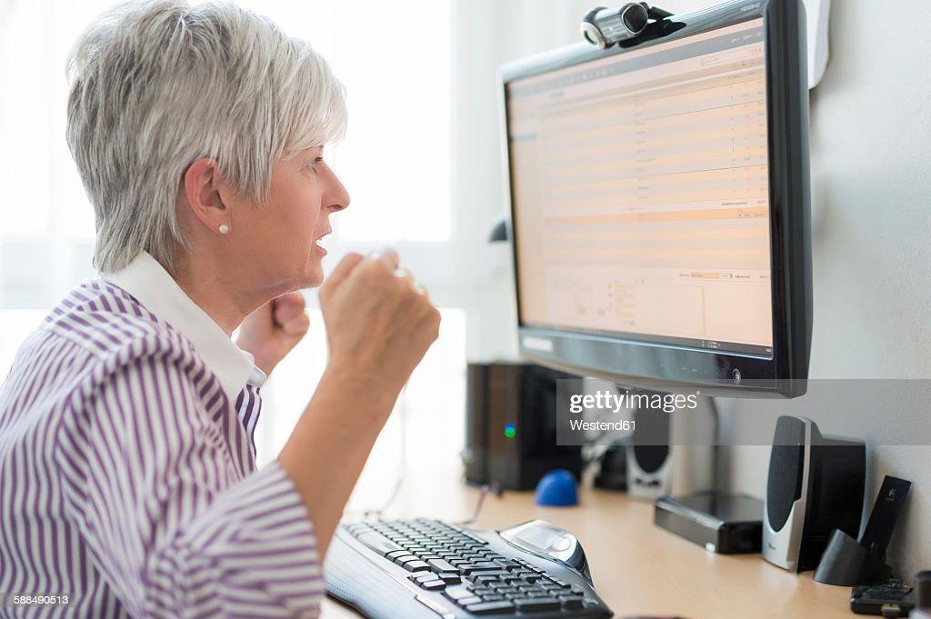 Senior woman looking horrified at computer monitor