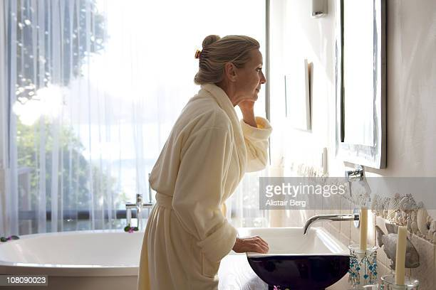 Senior woman looking in bathroom mirror