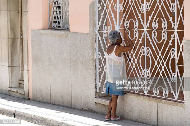 Senior woman looking inside her home holding iron grill Cuba has a high percentage of old people in their total population