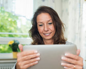 Senior woman looking on tablet, smiling
