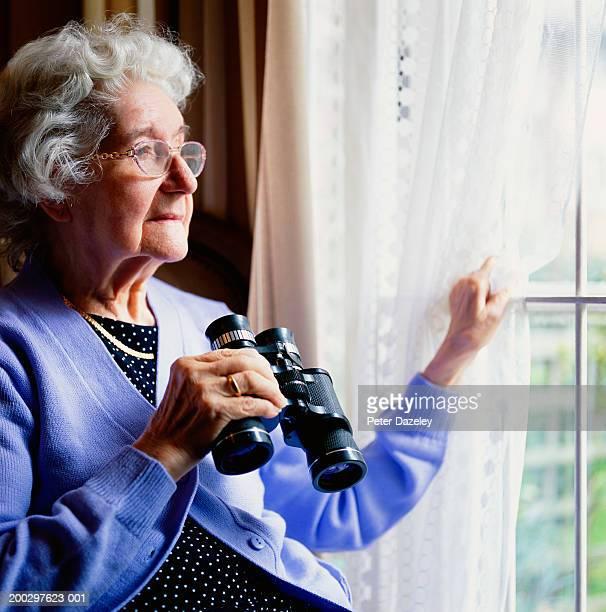 Senior woman looking out window, holding binoculars