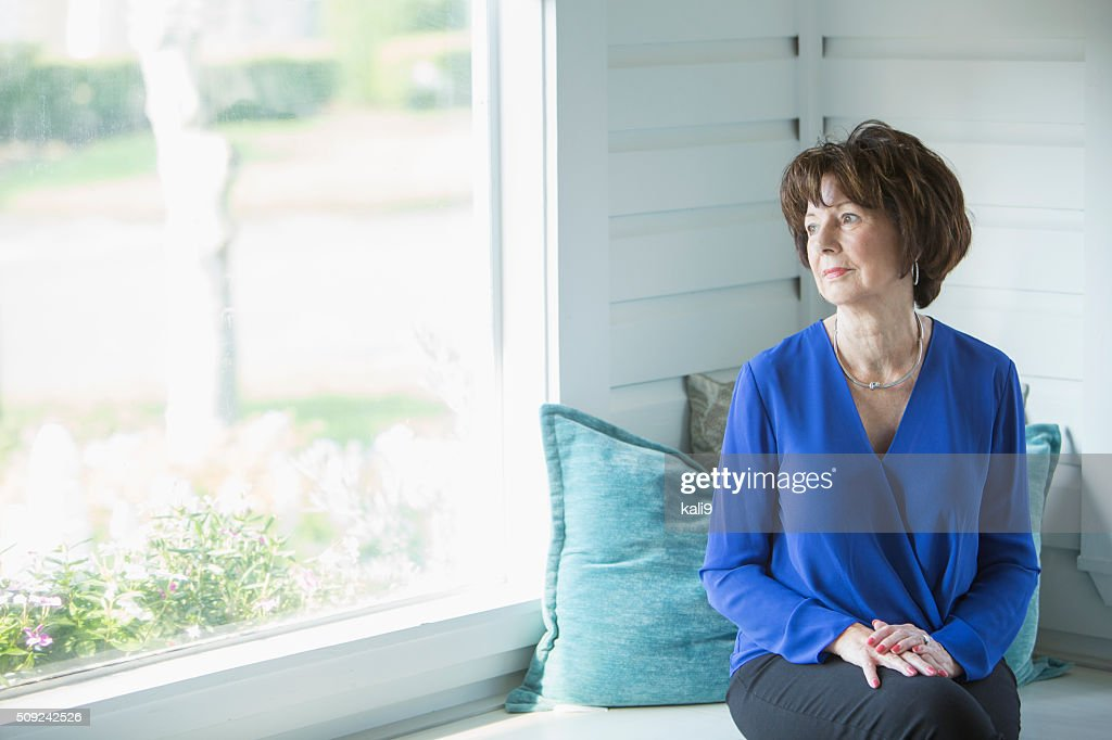 Senior woman looking out window with serious face : Stock Photo
