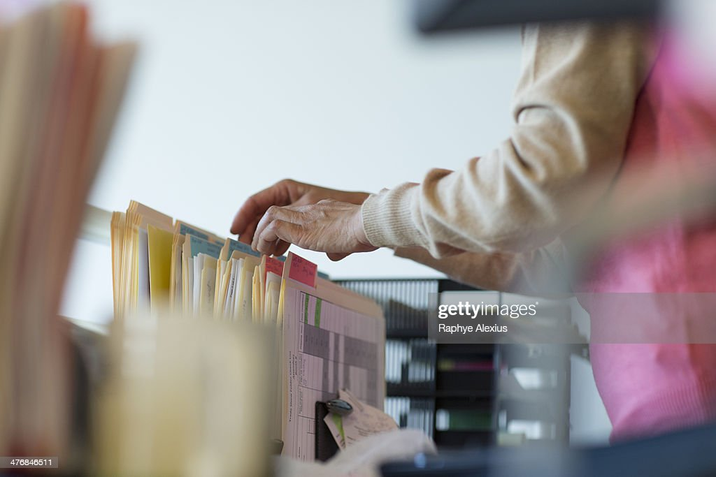 Senior woman looking through filing cabinet