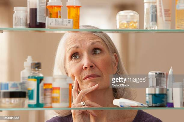 Senior woman looking through medicine cabinet