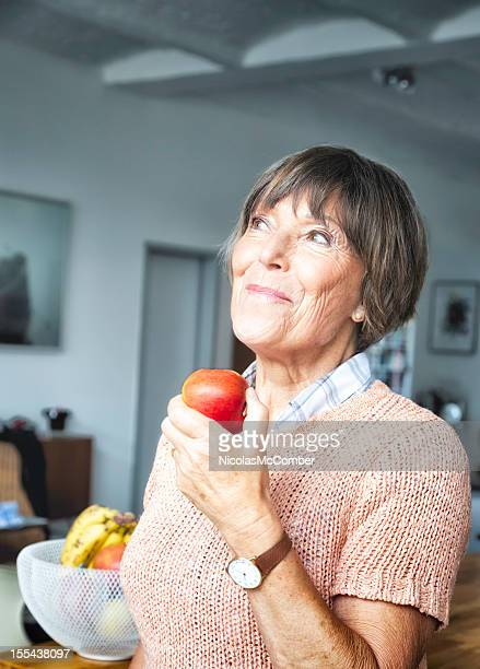 Senior woman looking up smiling while eating apple