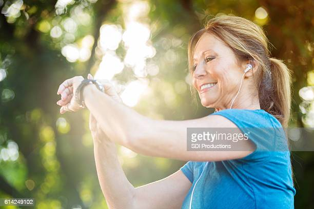 Senior woman looks at fitness tracker after workout