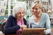 Senior Woman Looks At Photo Frame With Mature Female Neighbor