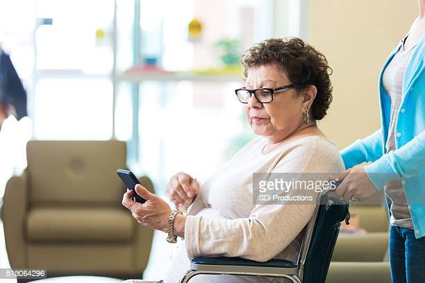 Senior woman looks at smart phone in nursing home