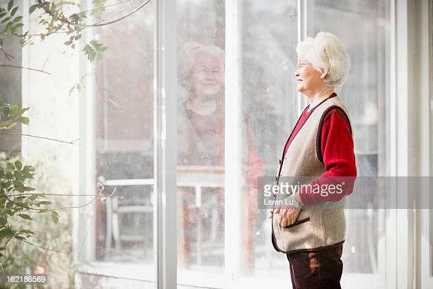 Senior woman looks through view window