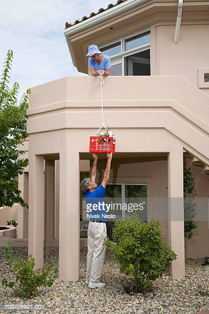 Senior woman lowering plant in basket to senior man