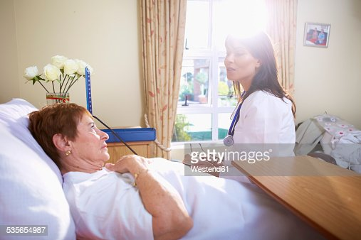 Senior woman lying in hospital bed talking to doctor