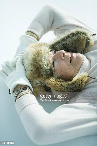Senior woman lying in snow