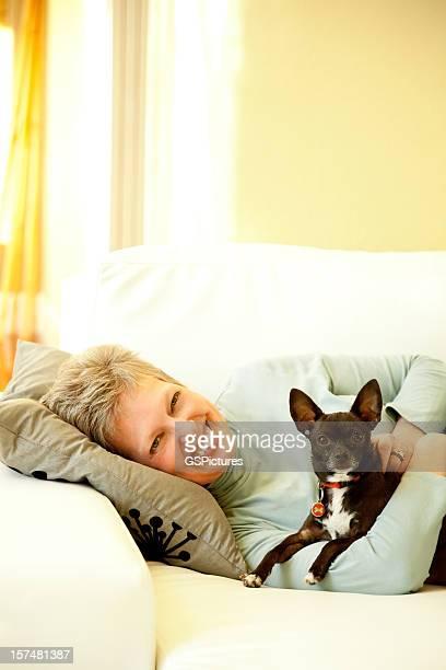 Senior Frau entspannt auf der Couch mit Ihrem Hund