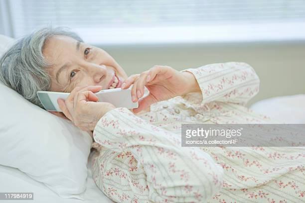 Senior woman lying on bed talking on cell phone, Kanagawa Prefecture, Honshu, Japan