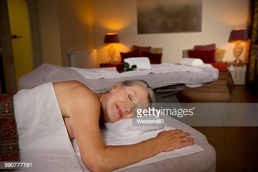 Senior woman lying on massage table with closed eyes